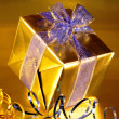 Elegant gold present with blue ribbons on gold — Stock Photo #3222121