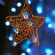 Gold star ornament with Christmas lights in back — Stock Photo #3222151