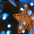 Gold star ornament with Christmas lights in back — Stock Photo #3222161