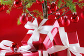 Elegant red presents under Christmas tree with d — Stock Photo