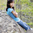 Little girl sitting against rock, smiling — Stock Photo #3253315