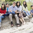 Stock Photo: Family sitting together on rocky ledge