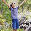 Teenage boy raising hands in praise — Stock Photo
