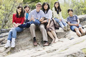 Family sitting together on rocky ledge — Stock Photo