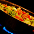 Chicken and vegetable stirfry in a wok; - Stock Photo