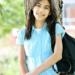Young teen girl standing with backpack by tree, smiling. Part as — Stock Photo #3519146
