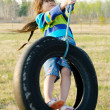 Little girl on tire swing - Stock Photo