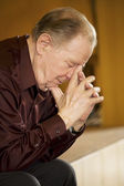 Elderly man praying in church — Stock Photo