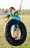 Little girl on tire swing — Стоковое фото