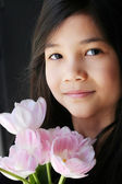 Girl holding pink tulips — Stock Photo