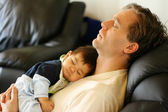 Baby sleeping on dad's chest — Stockfoto