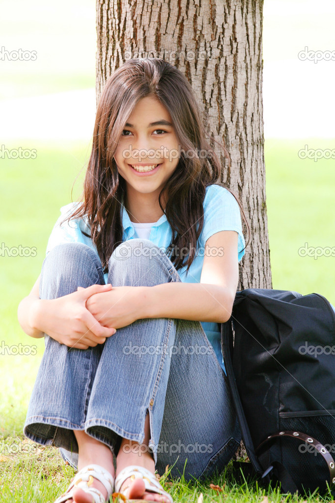 Young teen girl sitting against tree with backpack.