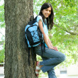 Young teen girl standing with backpack by tree, smiling. Part as - 图库照片