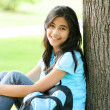 Young teen girl sitting against tree with backpack - Stok fotoğraf