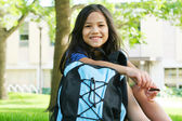 Girl sitting with her backpack in front of school — Stock Photo