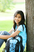 Young teen girl sitting against tree with backpack — Foto de Stock