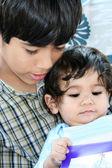 Big brother lecture au petit frère — Photo