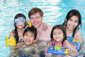 Family swimming in pool — Stock Photo