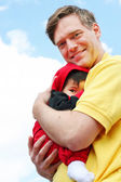 Baby cuddled safely in dad's arms — Stock Photo