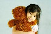 Child hugging her teddy bear — Stock Photo