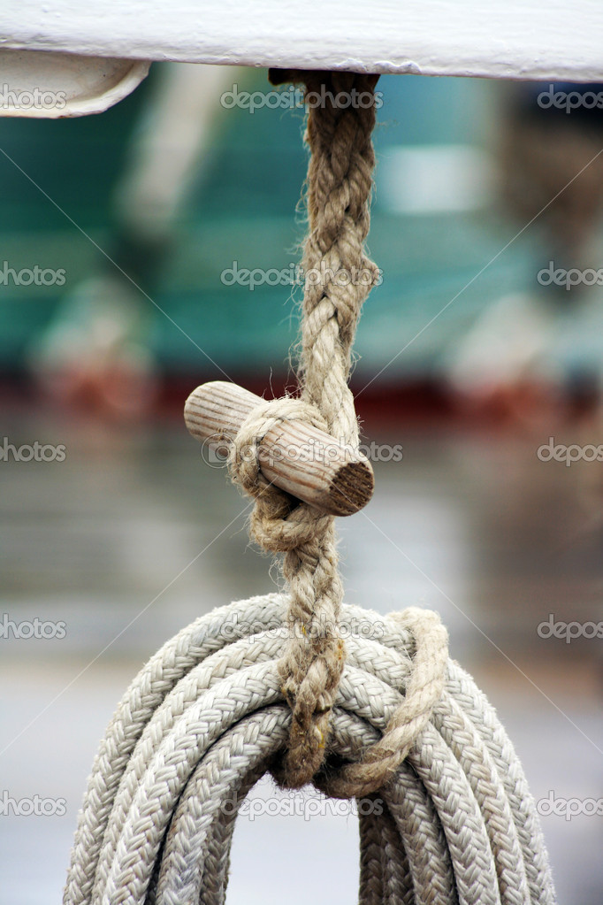 A neatly reel of boats rope tied and fastened with additional rope/twine and a wooden fixing hanging from the bow of a boat. — Stock Photo #3771239