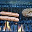 Hotdogs and hamburger grilling — Stock Photo