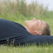 Young man lying in the grass — Stock Photo
