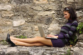 Sexy brunette woman using laptop — Photo