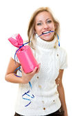 Beautiful young woman bites a gift — Stock Photo