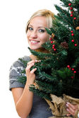 Cute woman smiling and holding a christmastree — Stock Photo
