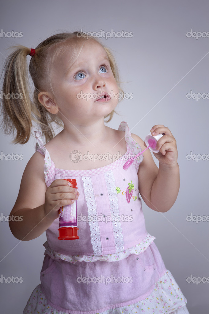 Blonde little girl playing with soap bubbles — Stock Photo #3542392