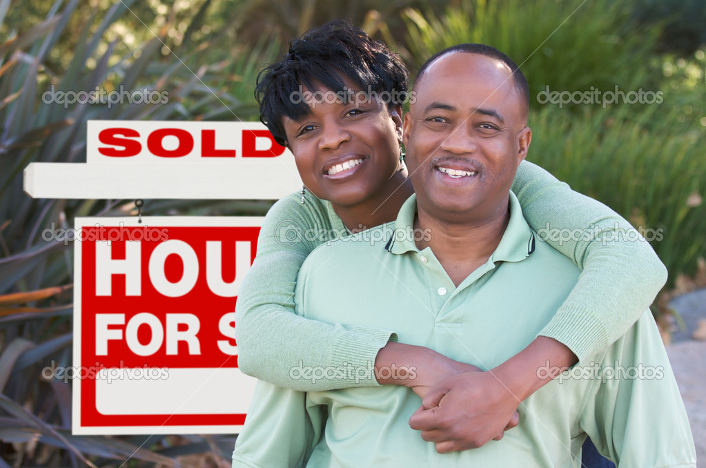 Happy African American Couple in Front of Sold Home For Sale Real Estate Sign. — Stock Photo #2814411