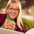 Foto Stock: Smiling Woman with Cup Using Laptop