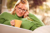 Lachende vrouw met beker met behulp van laptop — Stockfoto