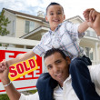 Father and Son in Front of Sign and Home — Stock Photo