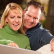 Handsome Happy Couple Using Their Laptop - Stock Photo