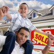 Foto de Stock  : Hispanic Father and Son with Sold Sign