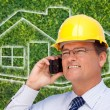 Contractor on Cell Phone Over House - Foto de Stock