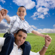 Happy Hispanic Father and Son Over Grass - Stock Photo