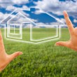 Stock Photo: Hands Framing House Over Grass Field