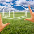 Hands Framing House Over Grass Field - Foto Stock