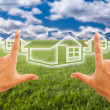 Hands Framing Houses Over Grass Field - Foto Stock