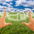 Hands Framing Houses Over Grass Field - Stock Photo