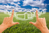 Hands Framing Houses Over Grass Field — Stock Photo