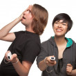 Diverse Couple with Video Game Controllers Having Fun Isolated on White - Stockfoto