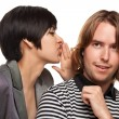 Attractive Diverse Couple Whispering Secrets Isolated on a White Background - Stock Photo