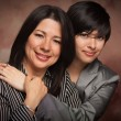 Attractive Multiethnic Mother and Daughter Studio Portrait on a Muslin Back - Stockfoto