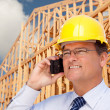Contractor in Hardhat at Construction Site Talks on His Cell Phone. — Foto de Stock