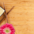 Gerber Daisy, Chopsticks and Dish on a Bamboo Background with Copy Space. — Stock Photo