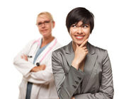 Female Doctor and Young Multiethnic Woman Isolated on a White Background. — Stock Photo